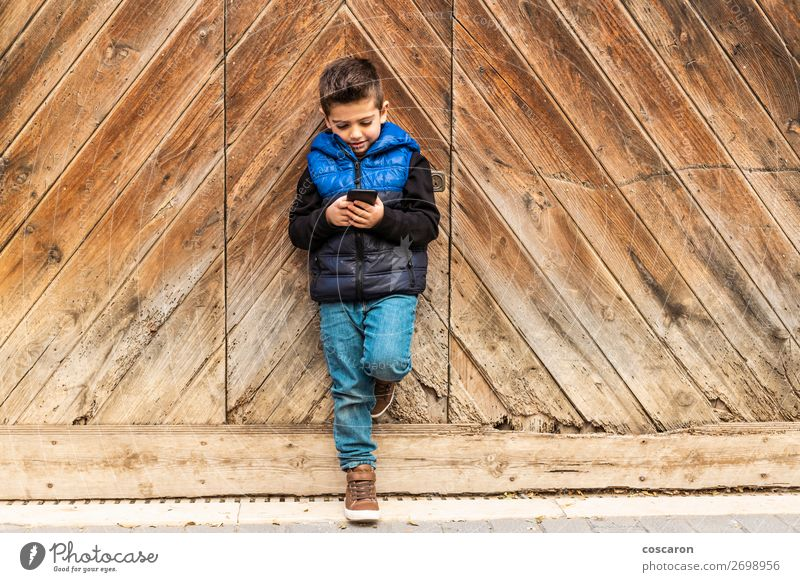 Little boy with a mibile phone with a wooden door background Beautiful Playing Vacation & Travel House (Residential Structure) Child Telephone Cellphone PDA