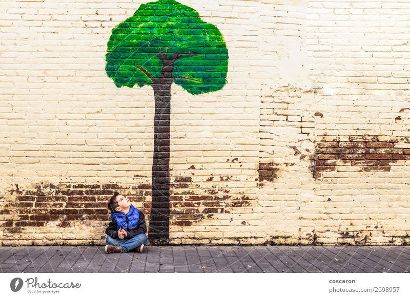 Little kid seated under a tree painted on a wall Child Human being Vacation & Travel Nature Summer Town Beautiful Green Landscape Tree Relaxation Leaf Joy