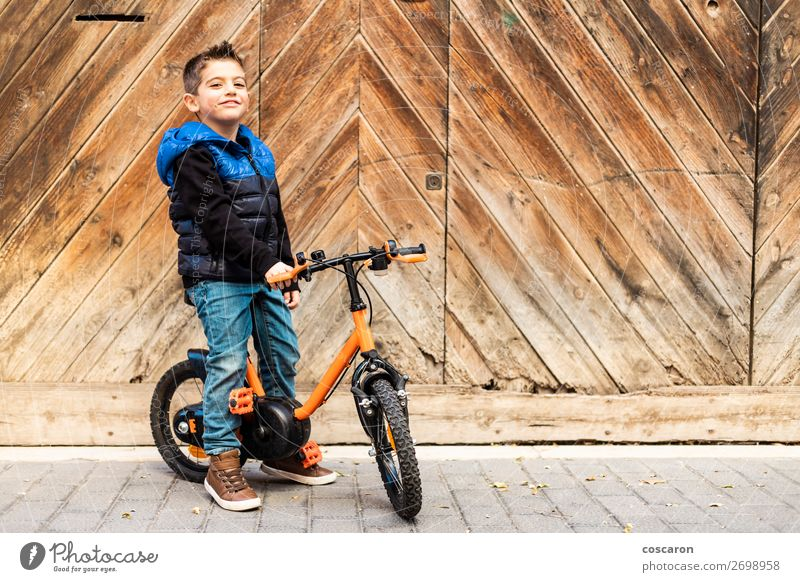 Litle boy with a bike on a wooden door background Child Human being Vacation & Travel Blue Town Beautiful House (Residential Structure) Relaxation Joy Face