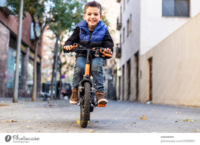Little kid riding his bicycle on city street Lifestyle Joy Happy Beautiful Face Relaxation Leisure and hobbies Playing Children's game Summer Sun Sports Success