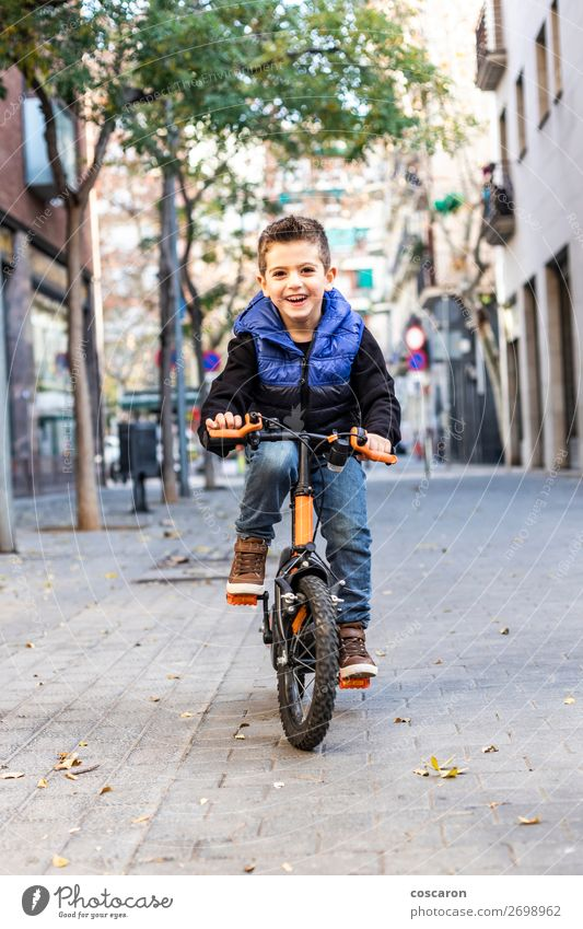 Little kid riding his bicycle on city street Lifestyle Joy Happy Beautiful Relaxation Leisure and hobbies Playing Children's game Sun Winter Sports Cycling