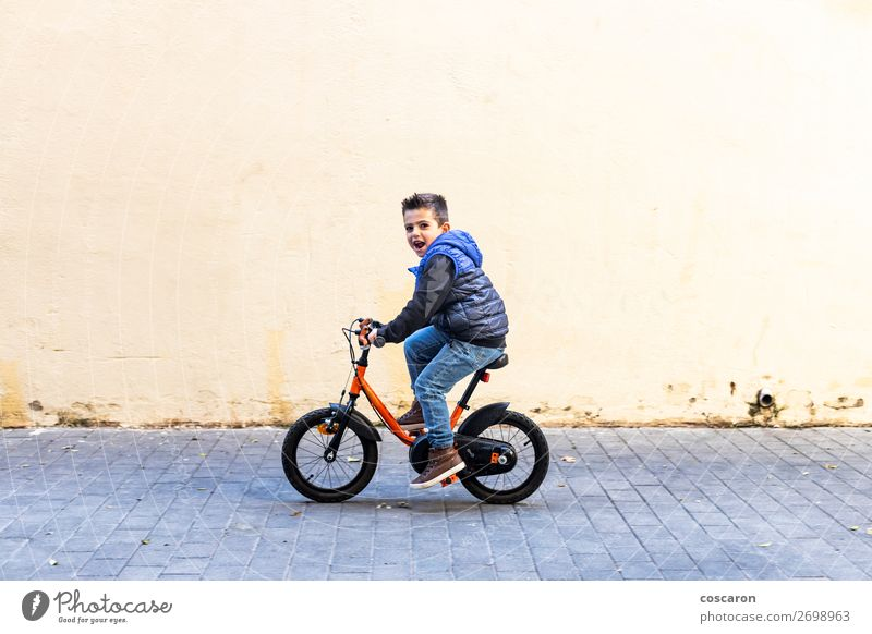 Little kid riding his bicycle on city street Child Human being Summer Blue Town Beautiful White Sun Relaxation Joy Street Lifestyle Wall (building) Sports