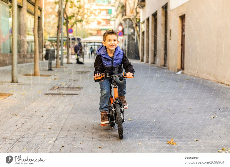 Little kid riding his bicycle on city street Child Human being Nature Blue Town Beautiful Sun Relaxation Joy Winter Face Street Lifestyle Sports Movement
