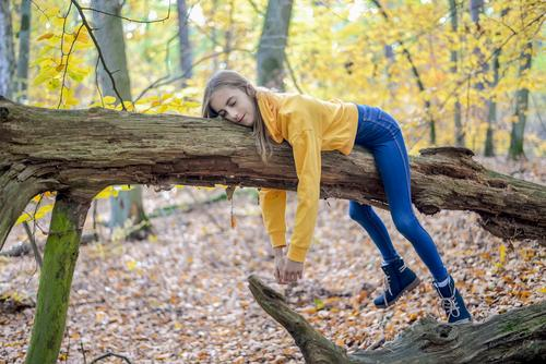 Girl lies on tree Lifestyle Joy Happy Contentment Relaxation Calm Leisure and hobbies Trip Child Nature Tree Forest Dream Sadness Hope Boredom Longing