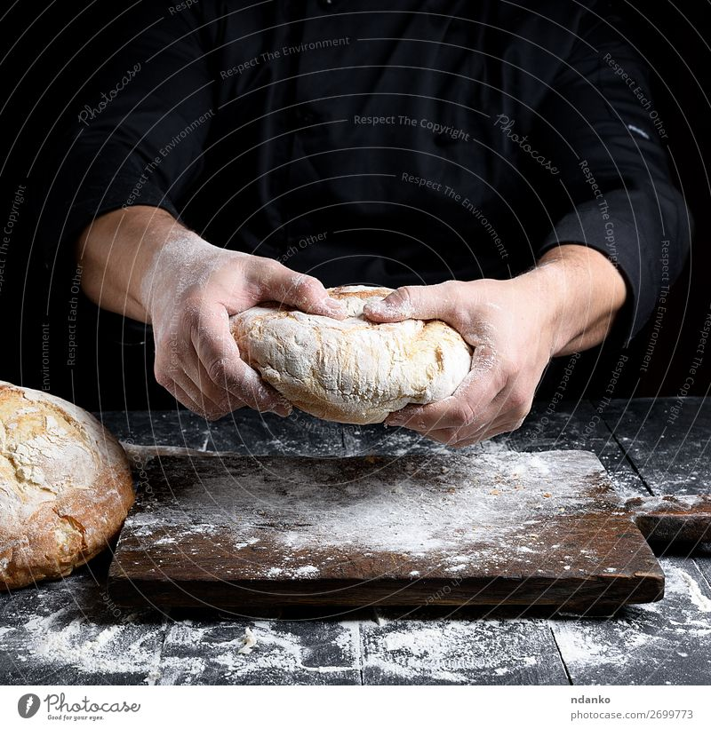male chef hands hold a whole loaf of baked round bread Bread Nutrition Table Kitchen Human being Hand Make Dark Fresh Brown Black White Tradition Baking Baker
