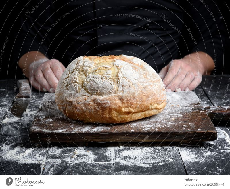 round baked homemade bread Dough Baked goods Bread Knives Table Kitchen Profession Cook Hand Wood Eating Make Dark Fresh Brown Black White Tradition Preparation