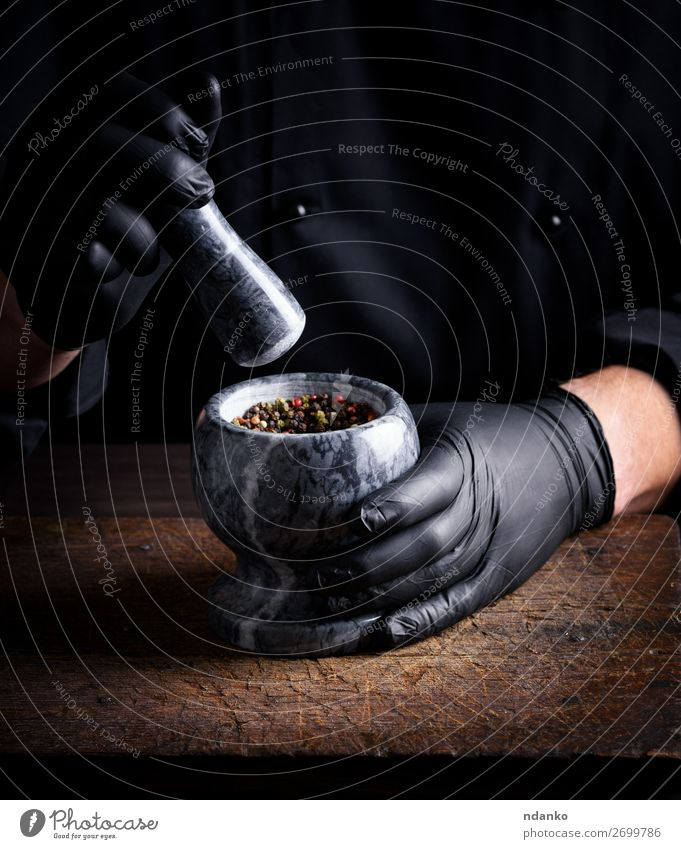 Chef in black latex gloves holds a stone mortar Herbs and spices Table Kitchen Work and employment Cook Tool Human being Man Adults Hand Gloves Stone Wood Dark