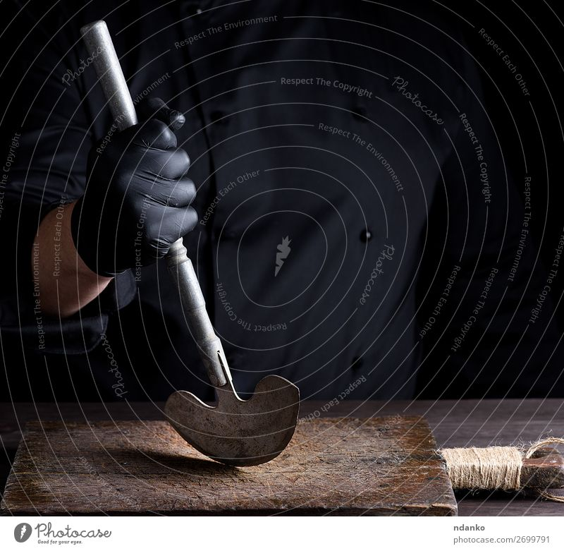 chef in black clothes holds in his hand a metal old knife Knives Kitchen Profession Cook Hand Gloves Metal Steel Old White board cleaver butcher Hold chopping