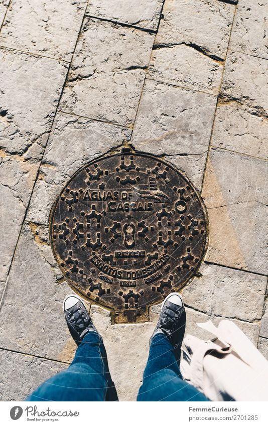 Woman stands on manhole cover in Cascais Feminine 1 Human being Vacation & Travel Gully Portugal Symbols and metaphors Sneakers Jeans Tourism Vacation photo Sun