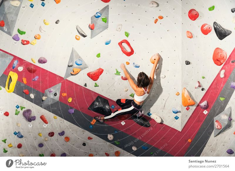 Woman practicing rock climbing on artificial wall indoors. Climber Climbing Rock Wall (building) Gymnasium Youth (Young adults) Fitness Sports