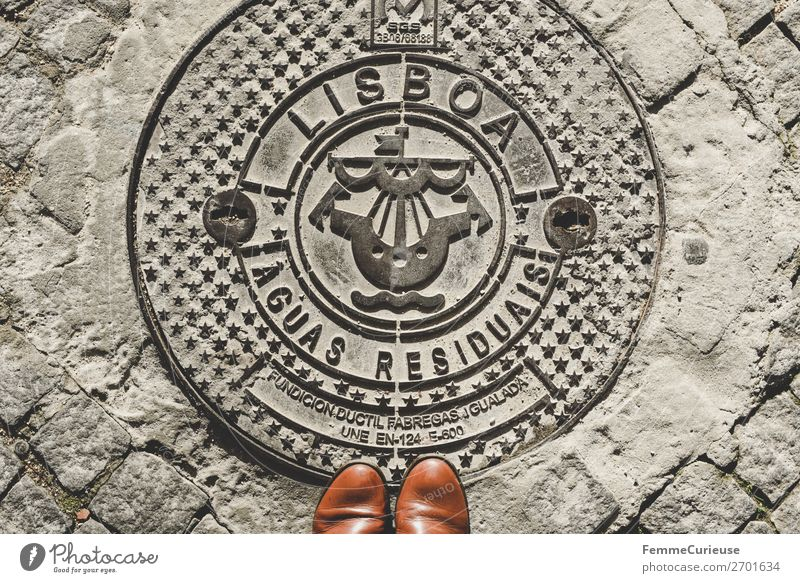Woman standing on manhole cover in Lisbon Town Vacation & Travel Gully Boots toe Sunbeam Symbols and metaphors Street Bird's-eye view Travel photography Tourism