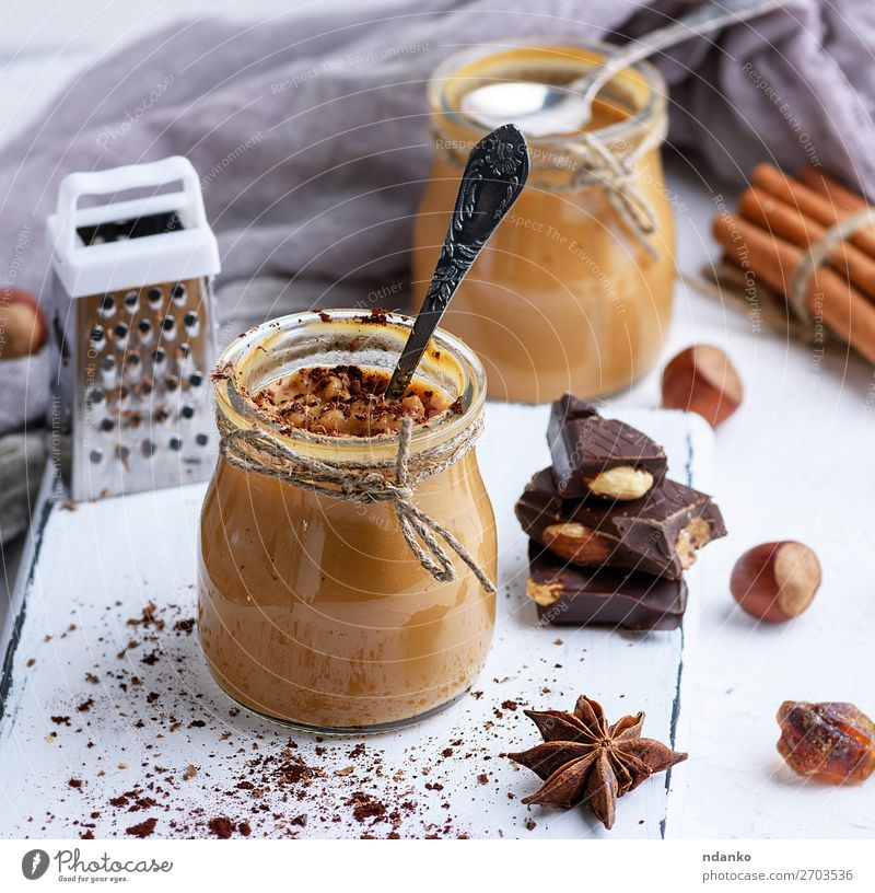 Caramel dessert Toffee in a glass jar Dessert Candy Herbs and spices Spoon Table Wood Fresh Delicious Brown cup background cream food Home-made Ingredients