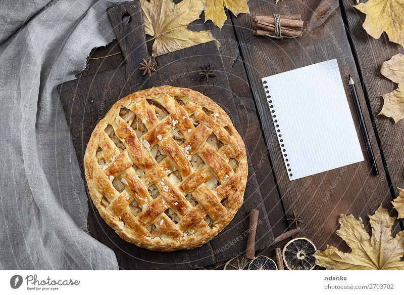 round apple pie on a brown wooden board Fruit Cake Dessert Candy Dinner Table Kitchen Autumn Leaf Paper Pen Wood Above Brown Yellow White Tradition American