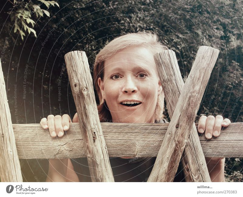 curious woman looks surprised over the garden fence Woman Adults Head 1 Human being Communicate Smiling Looking Curiosity Joy Happiness Surprise Marvel Fence