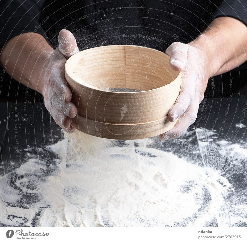 Chef in a black uniform holds in his hand a sieve Dough Baked goods Bread Nutrition Table Kitchen Human being Man Adults Hand Sieve Wood Movement Make Fresh