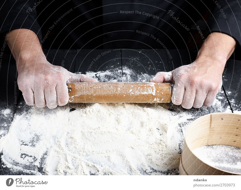 wooden rolling pin in men's hands Human being White Hand Black Wood Work and employment Fresh Table Kitchen Baked goods Cooking Bread Make Meal Baking Dough