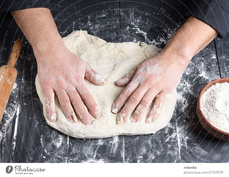 men's hands knead a round piece of dough for making pizza Dough Baked goods Bread Nutrition Bowl Table Kitchen Work and employment Cook Human being Man Adults