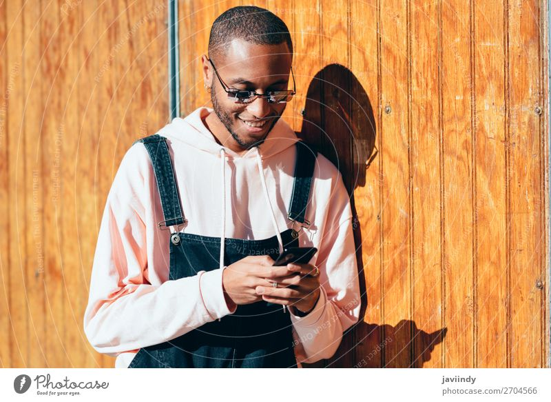 Young black man using smart phone outdoors Lifestyle Happy Beautiful Telephone PDA Technology Human being Masculine Young man Youth (Young adults) Man Adults 1