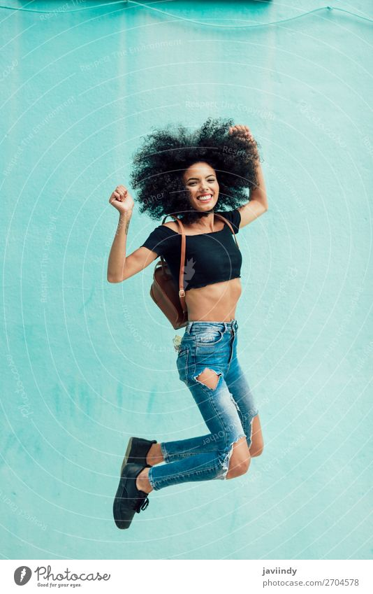 Young mixed woman with afro hair jumping outdoors. Lifestyle Style Happy Hair and hairstyles Face Human being Feminine Young woman Youth (Young adults) Woman