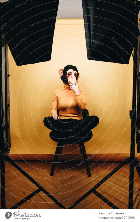 Woman with monkey mask sitting thoughtfully in photo studio Feminine Adults 1 Human being 18 - 30 years Youth (Young adults) 30 - 45 years Joy Monkeys