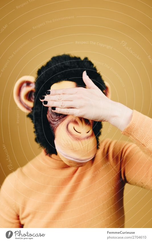 Woman with monkey mask holding her hand in front of her face Feminine Adults 1 Human being 18 - 30 years Youth (Young adults) 30 - 45 years Yellow Monkeys
