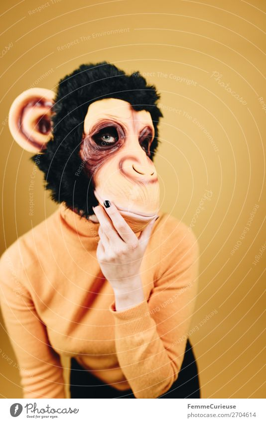Woman with monkey mask posing against a yellow background Feminine Adults 1 Human being 18 - 30 years Youth (Young adults) 30 - 45 years Joy Funny Mask Carnival