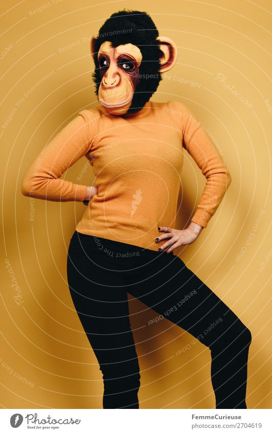 Woman with monkey mask posing against a yellow background Feminine Adults 1 Human being 18 - 30 years Youth (Young adults) 30 - 45 years Joy Monkeys Chimpanzee