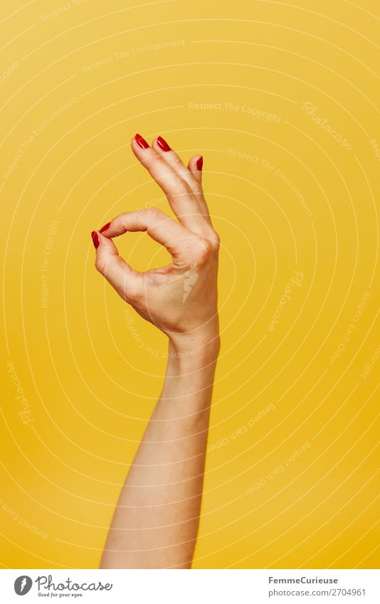 Hand signal for okay against a yellow background Feminine 1 Human being Sign Communicate OK Gesture Fingers Underarm Yellow Red Nail polish right-handed