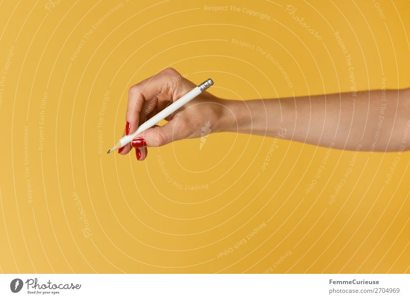 Forearm and hand with pencil against a yellow background Feminine 1 Human being Communicate Hand Fingers Nail polish Red Yellow Draw Write Pencil Underarm