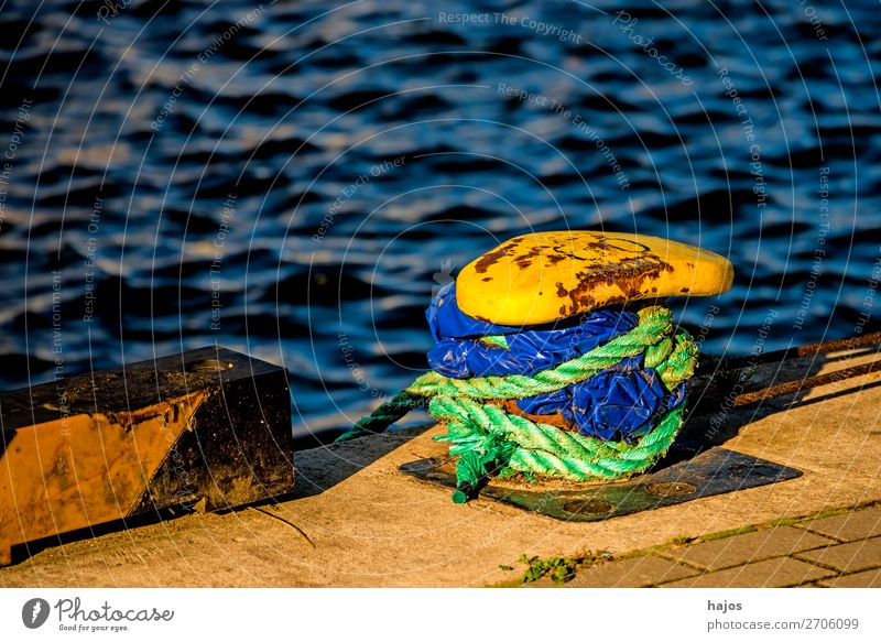 Harbour bollard with mooring rope Design Maritime Blue Yellow Bollard harbour bollards mooring lines Green Water Baltic Sea pier Navigation lash anchored fixed