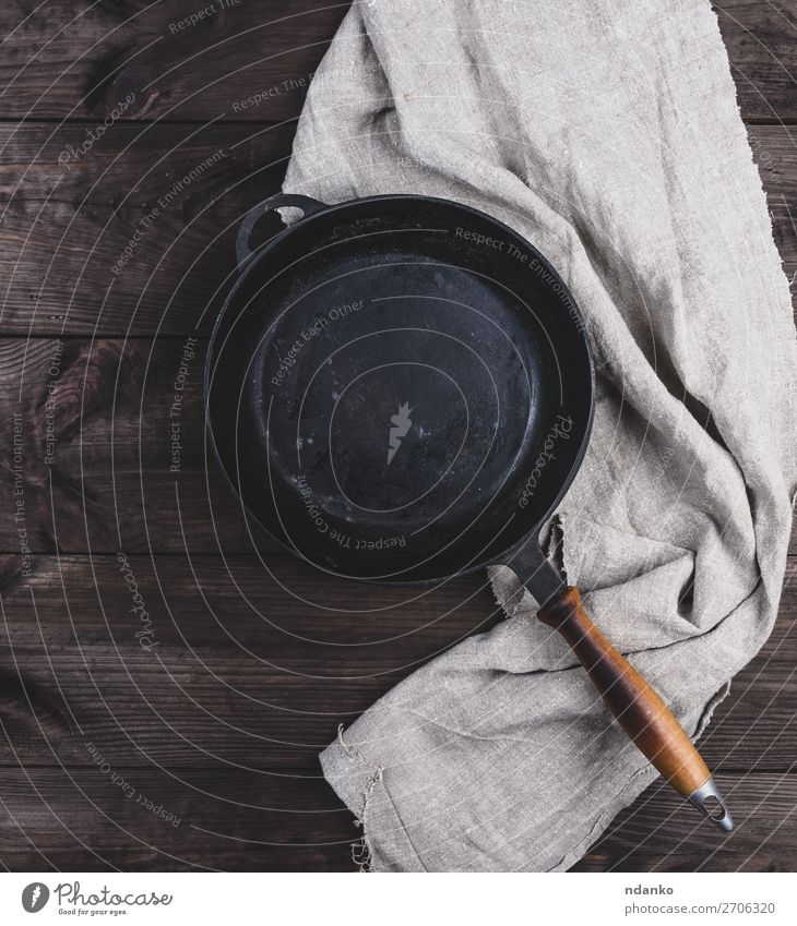 empty black round frying pan with wooden handle Dinner Pan Table Kitchen Wood Metal Old Dark Above Clean Brown Black vintage background board Cast cooking