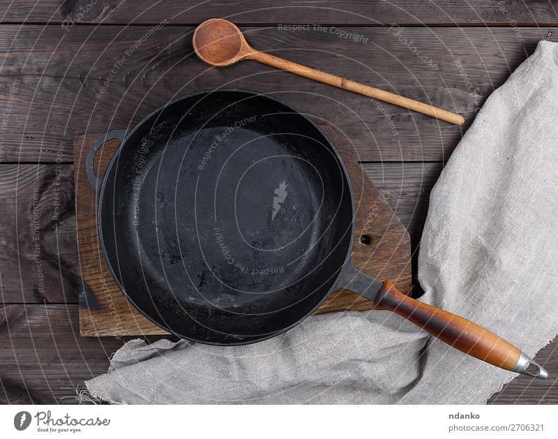 empty black round pan with wooden handle Dinner Pan Spoon Table Kitchen Wood Metal Old Dark Above Clean Black Frying background iron Cast Vantage point skillet
