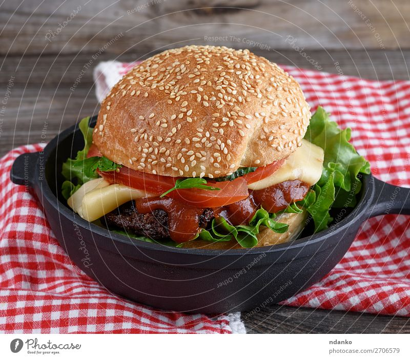 burger with a meatball and vegetables Meat Cheese Vegetable Bread Roll Lunch Dinner Fast food Pan Table Wood Eating Fresh Large Delicious Green Red Black