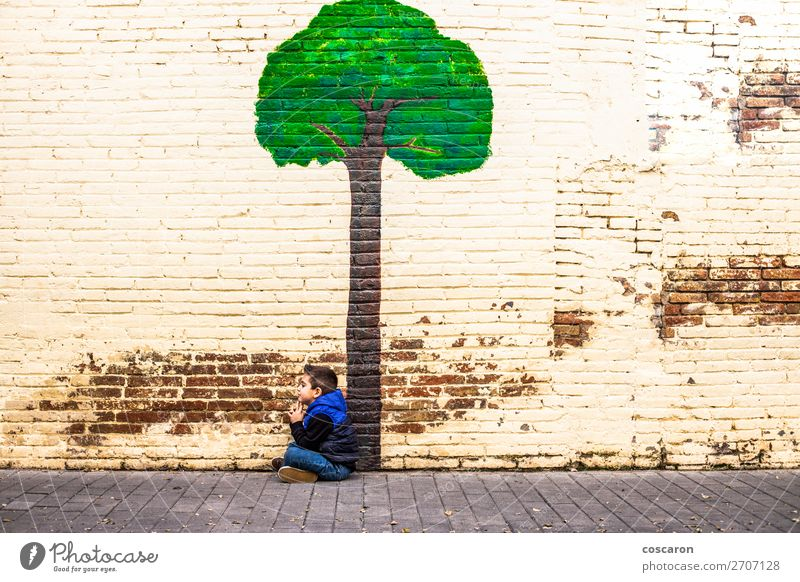 Little kid seated under a tree painted on a wall Child Human being Nature Blue Town Beautiful Green Landscape Tree Leaf Joy Forest Winter Wall (building)