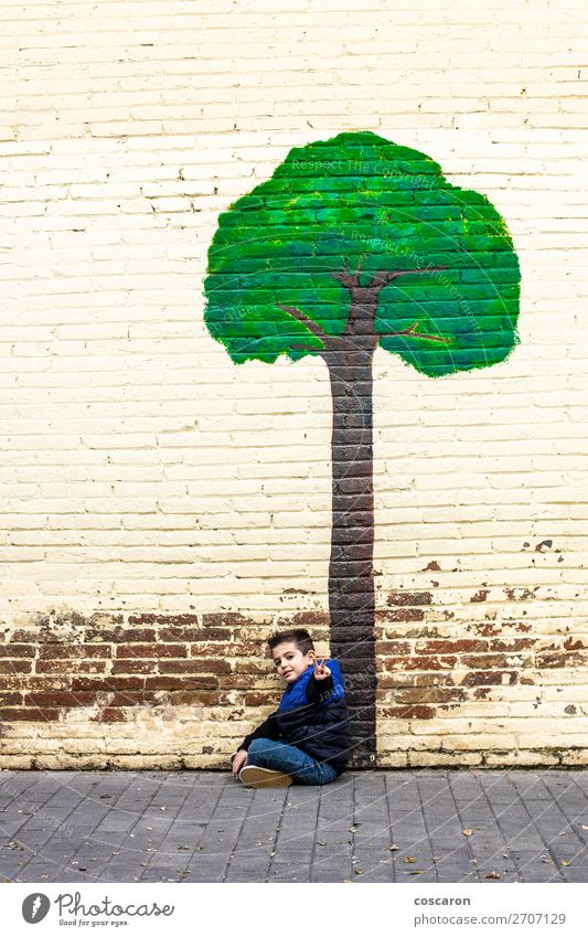 Little kid seated under a tree painted on a wall Child Human being Vacation & Travel Nature Blue Town Beautiful Green Landscape Tree Leaf Joy Forest Winter