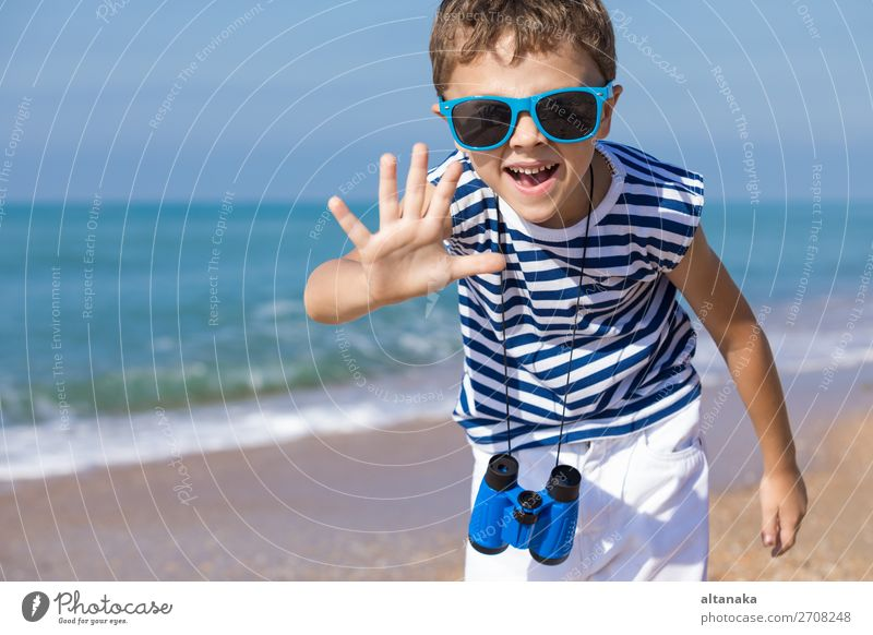 One happy little boy playing on the beach at the day time. He are dressed in sailor's vest. Kid having fun outdoors. Concept of sailor on vacation. Lifestyle