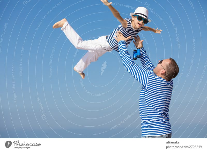 Father and son playing on the beach at the day time. They are dressed in sailor's vests. Concept of sailors on vacation and friendly family. Lifestyle Joy Happy
