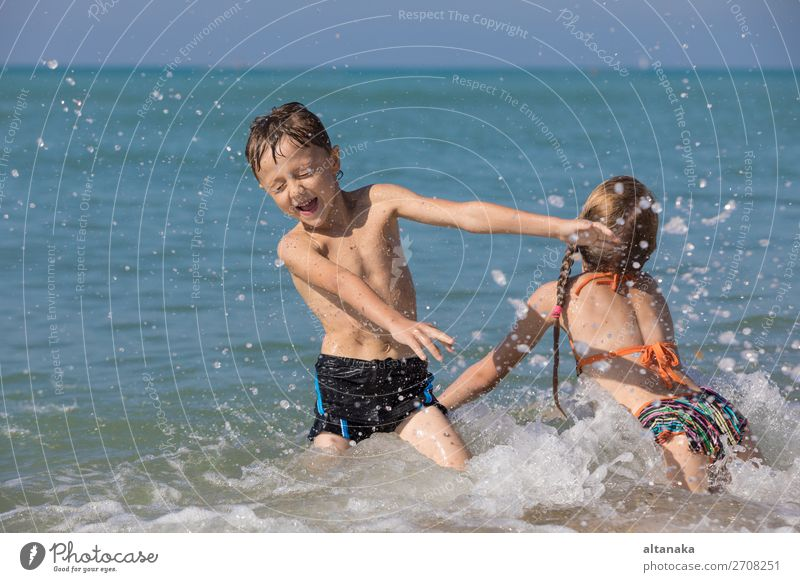 Happy children playing on the beach at the day time. Two Kids having fun outdoors. Concept of summer vacation and friendly family. Lifestyle Joy Beautiful
