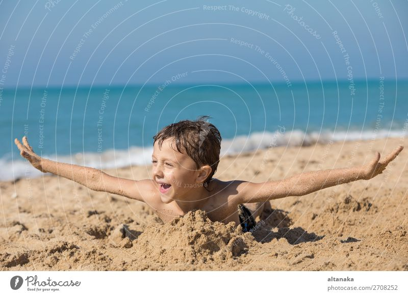 One happy little boy playing on the beach at the day time. Kid having fun outdoors. Concept of vacation. Lifestyle Joy Happy Beautiful Relaxation