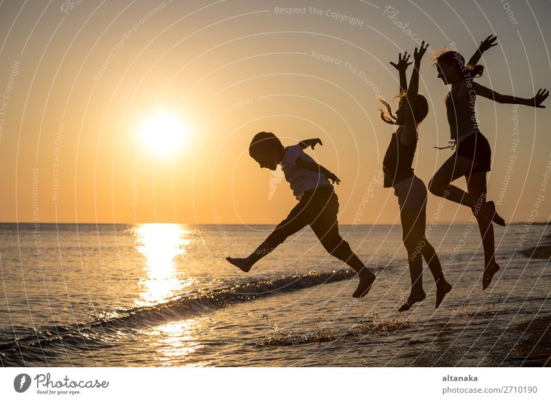 Happy children playing on the beach at the sunset time. Three Kids having fun outdoors. Concept of summer vacation and friendly family. Lifestyle Joy