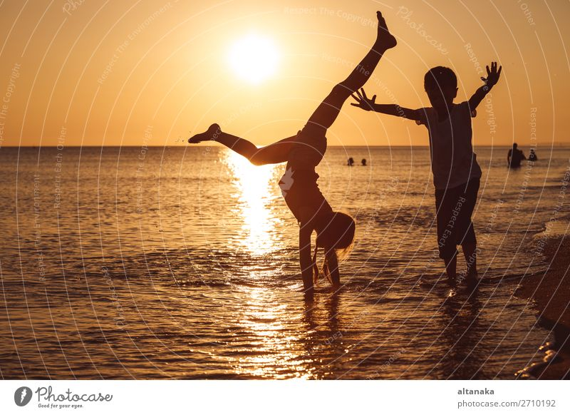 Happy children playing on the beach at the sunset time. Two Kids having fun outdoors. Concept of summer vacation and friendly family. Lifestyle Joy