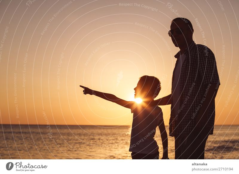 Father and son playing on the beach at the sunset time. People having fun outdoors. Concept of happy vacation and friendly family. Lifestyle Joy Happy