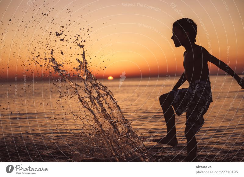 One happy little boy playing on the beach at the sunset time. Kid having fun outdoors. Concept of summer vacation. Lifestyle Joy Happy Beautiful Relaxation