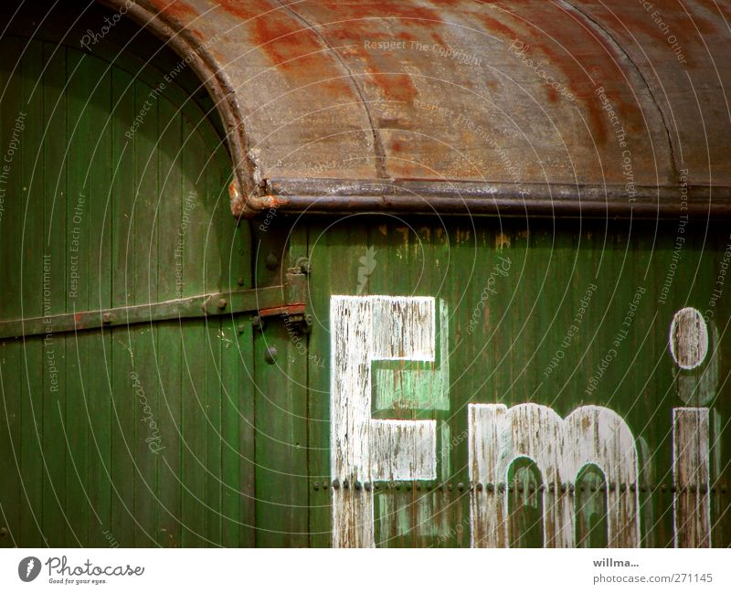 emi Letters (alphabet) Characters Text Old Historic Site trailer Trailer Railroad car Decline Past Transience Change Nostalgia Wooden wall Brown Green White