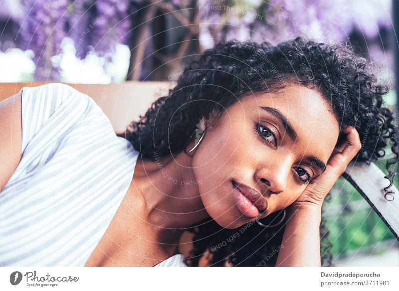 Young black woman laying down on a chair surrounded by flowers Woman Blossom Spring Lilac Portrait photograph multiethnic Black African Mixed race ethnicity