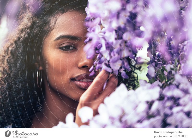 Thoughtful happy young black woman surrounded by flowers Woman Blossom Spring Lilac Close-up multiethnic Black African Mixed race ethnicity To enjoy Happy