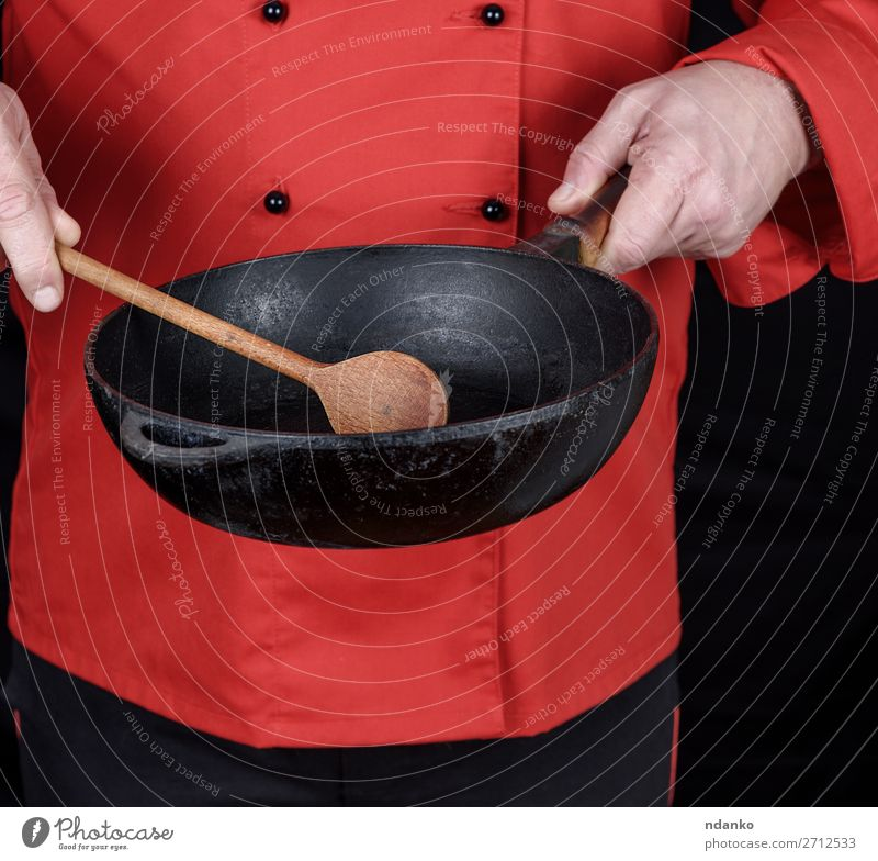cook in red uniform holding an empty black frying pan Pan Spoon Kitchen Restaurant Profession Cook Human being Man Adults Hand Clothing Red Black Cast iron