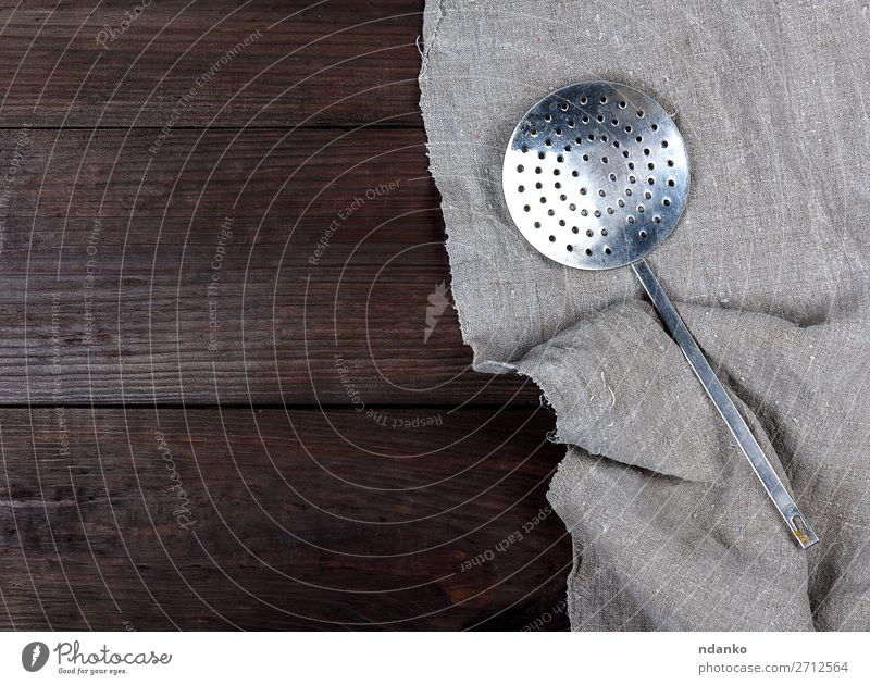 old iron kitchen skimmer on a gray linen napkin Spoon Kitchen Tool Wood Metal Steel Old Gray White strainer Grating silver Stainless equipment handle Household