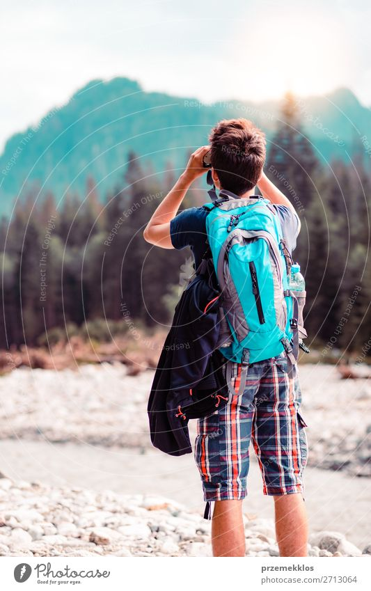 Young wanderer with backpack looks through a binoculars Lifestyle Leisure and hobbies Vacation & Travel Tourism Trip Summer Mountain Human being Boy (child)