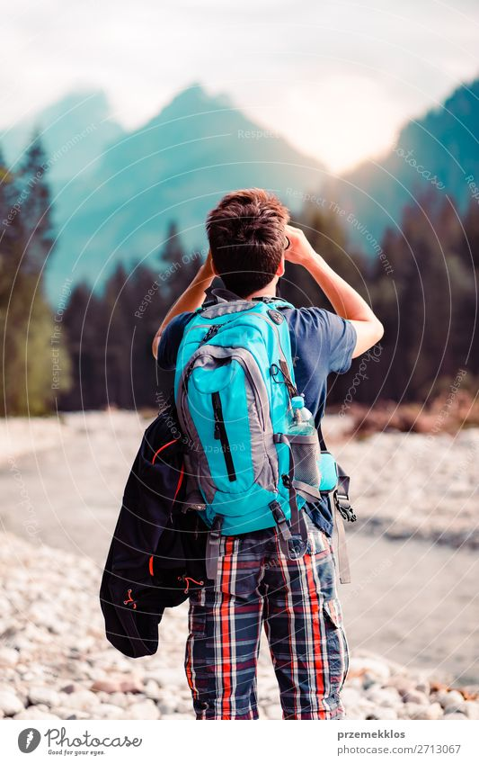 Young wanderer with backpack looks through a binoculars Lifestyle Leisure and hobbies Vacation & Travel Tourism Trip Adventure Summer Mountain Human being